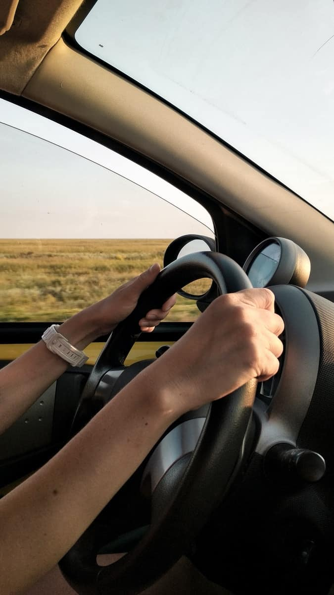 person with white watch driving car